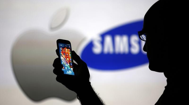 A man is silhouetted against a video screen with Apple and Samsung logos as he poses with a Samsung Galaxy S4 in this photo illustration taken in the central Bosnian town of Zenica, August 14, 2013. REUTERS/Dado Ruvic (BOSNIA AND HERZEGOVINA - Tags: BUSINESS TELECOMS) - RTX12L6K
